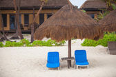 Blue beach loungers under thatched umbrellas on a rainy beach — Stock Photo