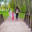 Young mother walking with her little daughter in autumn park — Stock Photo