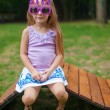 Cute little girl in purple Happy Birthday glasses sitting on wooden chair outdoor — Stock Photo