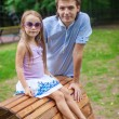 Portrait of father with his daughter sitting on the wooden plank bed in park — Stock Photo