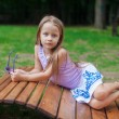 Cute little girl lying on wooden chair and relaxing outdoor in the park — Stock Photo #29807149