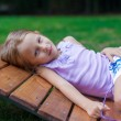 Cute little girl lying on wooden chair outdoor in the park — Stock Photo
