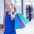 Little fashion girl with packages in a large shopping center — Stock Photo #29807267