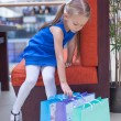Little fashion girl sits near packages in a large shopping center — Stock Photo #29807301