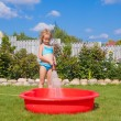 Happy little girl pouring water from a hose and laughing — Stock Photo