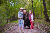 Young mother with her little daughters looking to camera oudoor — Stock Photo