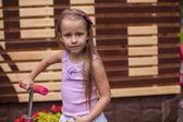 Adorable little girl on a scooter in children's park — ストック写真