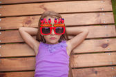 Adorable little girl in glasses with the words Happy Birthday outdoors — Stock Photo