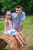Portrait of father with his daughter sitting on the wooden plank bed in park — Stok fotoğraf