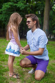Young happy father talking with cute daughter in the park — Stock Photo
