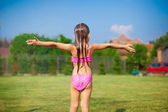 Back view of little girl in a swimsuit playing and splashing — Stock Photo