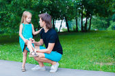 Young father pities his little daughter, who hurt her leg — Stock Photo