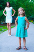 Close-up of little fashion girl on background of young mother — Stock Photo