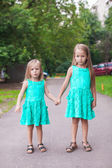 Two little fashion sister walking together on street — Stock Photo