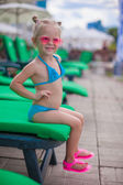 Little happy girl on the loungers by pool looking at camera — Stock Photo