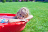 Portrait charming little girl enjoying her vacation in the pool outdoors — Stock Photo