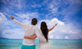 Back view of young couple spread their arms standing on white sandy beach — Stock Photo