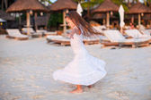 Adorable little girl in beautiful clothes dancing at sunset beach — Stock Photo