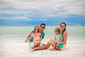 Young beautiful family with two daughters having fun at beach — Stock Photo