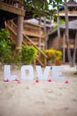 "Word ""love"" on the sandy beach at beautiful resort — Stockfoto"