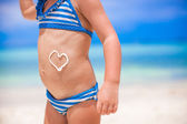 Close-up heart painted by sun cream on little girl stomach — Stock Photo