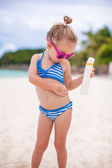Little adorable girl in swimsuit rubs sunscreen herself — Stock Photo