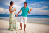 Young couple relaxing with two cocktails on sandy beach — Stock Photo