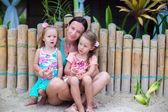 Mladá matka a dvě krásné dcery seděl na písku u plotu — Stock fotografie