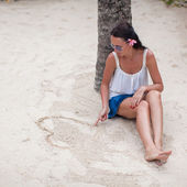 Young woman draws a heart in the sand with her finger — Stock Photo