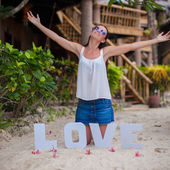 "Young girl sitting on sand with the word ""Love"" and spread her arms — Stock Photo"