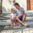 Young father with little daughters have a rest on street in old greek town — Stock Photo