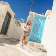 Happy young woman talking on phone and walking through the narrow old streets in Greek village of Emporio — Stock Photo