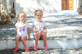 Young charming girls sitting at street in old Greek village of Emporio, Santorini — Stock Photo