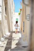 Bakifrån av bedårande flicka gå ensam i smala gator på emporio byn på ön santorini, grekland — Stockfoto