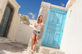 Happy young woman talking on phone and standing near blue door in the Greek village of Emporio — Stock Photo