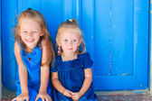 Closeup of Little adorable girls sitting near old blue door in Greek village, Emporio, Santorini — Stock Photo