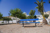 Blue bench on a large area in Greek village at Santorini — Stock Photo