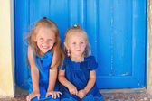 Portrait of Little adorable girls sitting near old blue door in Greek village, Emporio, Santorini — Stock Photo