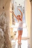 Charming young woman in the rays of light on empty street in the Greek city of Santorini — Stock Photo