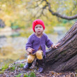 Stock Photo: Little cute girl in red hat having fun at autumn park