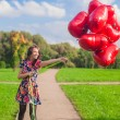 Young happy attractive womin beautiful dress have fun with red balloons outside — Stock Photo #32207267