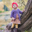 Stock Photo: Cute little girl in red cap near lake at autumn park