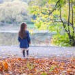 Little cute girl walks in a beautiful autumn park near the lake — Stok fotoğraf