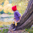 Cute little girl in a red cap near lake at the autumn park — Stock Photo #32209079