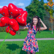 Young happy attractive woman in beautiful dress with red balloons walking outside — Stock Photo