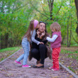 young mother with her little daughters having fun oudoor in autumn park — Stock Photo