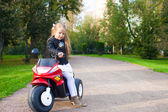 Little beautiful rock girl in leather jacket sitting on her toy motorcycle — Stok fotoğraf