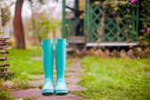 Bright mint rubber boots in the garden summer house background — Stock Photo