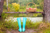 Bright mint rubber boots and straw basket on a small lake in the village — Zdjęcie stockowe
