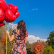 Back view of attractive young girl with red smiling balloons in hand outdoor — Stock Photo